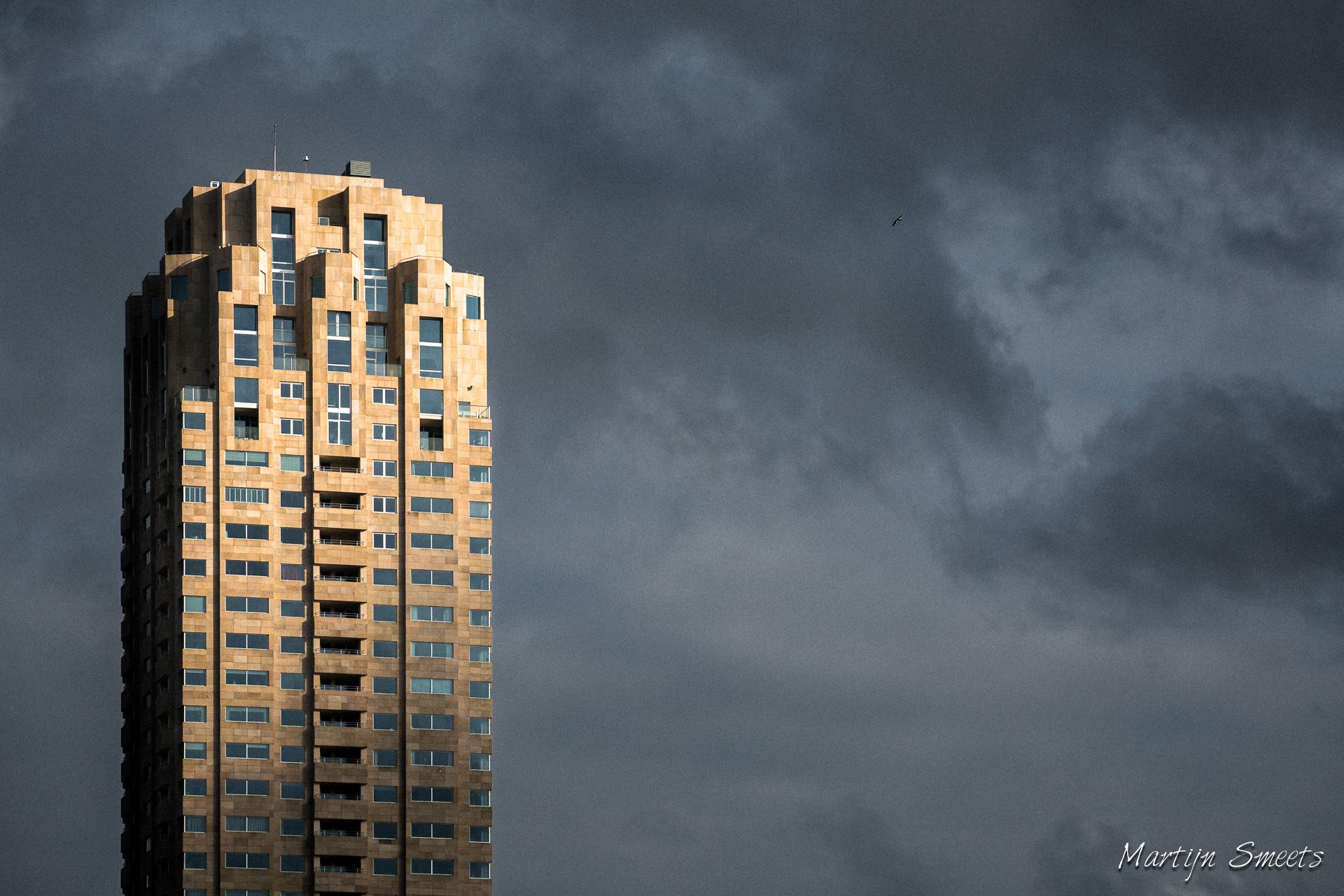 De woontoren New Orleans op de Wilhelminapier in Rotterdam wordt selectief belicht door de ondergaande zon.